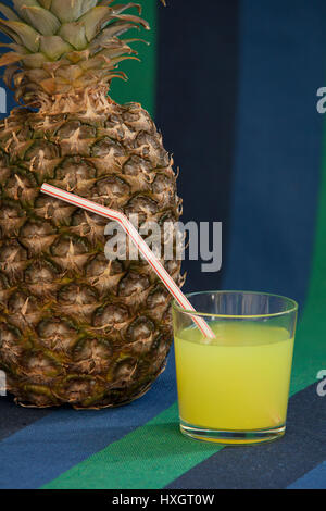 glass of juice with a straw near Pineapple - Stock Photo