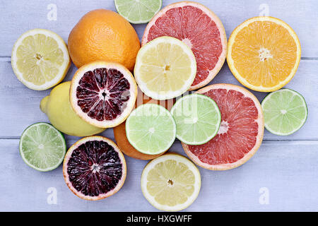 Variety of citrus fruits (orange, blood oranges, lemons, grapefruits, and limes) over a blue wood table top rustic - Stock Photo