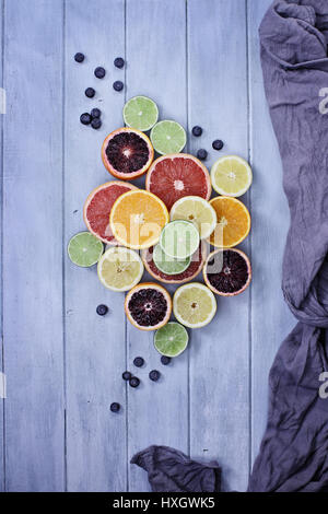 Variety of citrus fruits (orange, blood oranges, lemons, grapefruits, and limes) with blueberries with grey fabric - Stock Photo