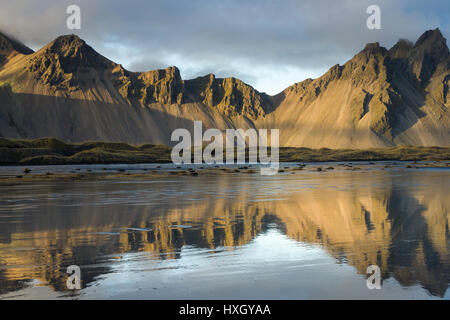 Stokksnes and Vestrahorn mountains with clouds above them reflected in water in late afternoon light, Iceland - Stock Photo
