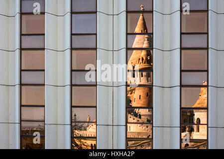 Reflection of one of the towers of the Fishermen's Bastion in the modern glass frontage of the Hilton Hotel, Várhegy, - Stock Photo