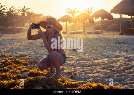 Young woman taking photo at sunset on sand beach - Stock Photo