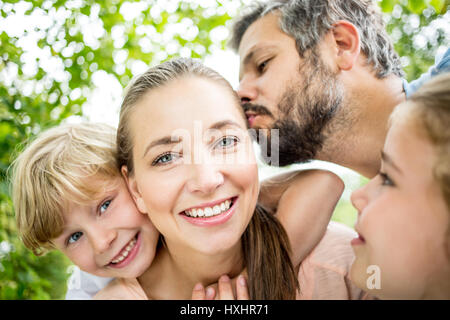 Happy family in love with father kissing mother - Stock Photo