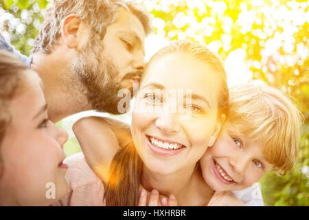 Family love with parents kissing and hugging their children - Stock Photo
