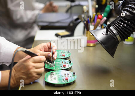 Electronics Manufacturing Services, Manual Assembly Of Circuit Board Soldering,  close-up of the hand women hold - Stock Photo