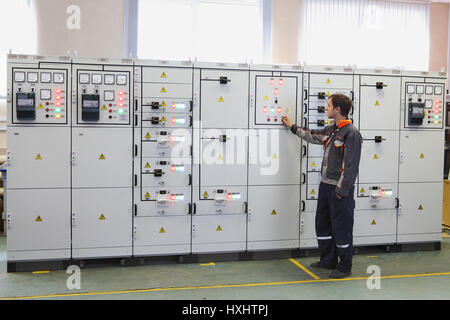 St. Petersburg, Russia - October 4, 2016: Engineer make Services electric transformer station or maintenance switchboard. - Stock Photo
