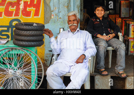 An old man and his grandson sit proudly outside their bicycle parts shop in Udaipur - Stock Photo