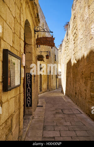 "MDINA, MALTA - JULY 29, 2015: The narrow medieval stone paved street with the restaurant ""Medina"" in the Mdina, - Stock Photo"
