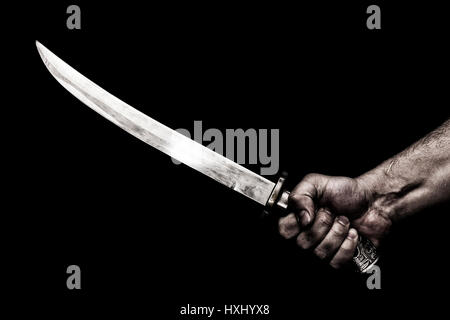 hand holding knife against plank wood - Stock Photo