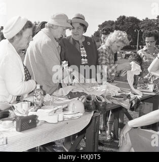 1960s, ladies looking through the various second-hand goods or bric-a-brac available on a stall at an outside jumble - Stock Photo