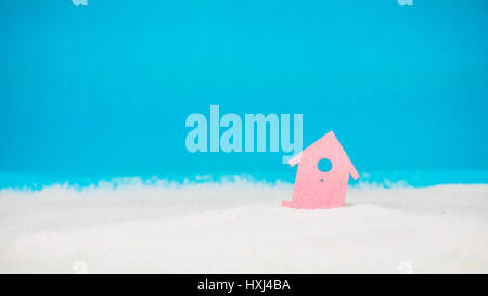 Symbol of little red house on the sand with bright blue background - Stock Photo