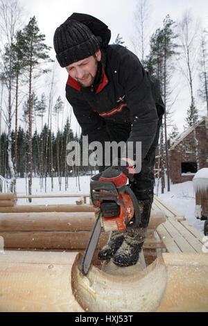 Leningrad Region, Russia - February 2, 2010: Builder handles log using chainsaw, He cut out round saddle notch. - Stock Photo