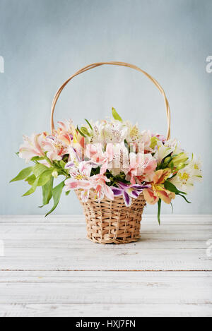 Bouquet alstroemeria in wicker basket on light blue background - Stock Photo
