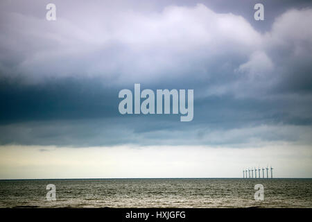 Stormy summer clouds over the Iris Sea with a line of wind turbines on the horizon viewed from the popular tourist - Stock Photo