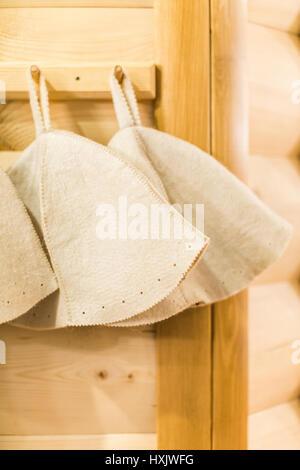Three Russian White Wool Hats for Sauna Banya Bath House on a wooden background close up. Bath accessories in traditional - Stock Photo