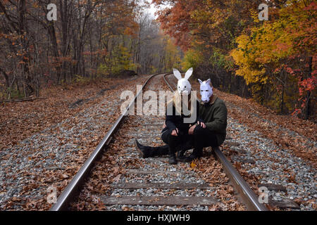 man and woman sitting in train tracks wearing a white horse and white rabbit mask - Stock Photo