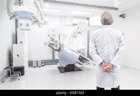 Senior doctor looking at CT (Computed tomography) scanner in hospital laboratory - Stock Photo