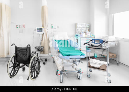 Empty wheelchair parked in hospital room with beds and comfortable medical equipped in a modern hospital - Stock Photo