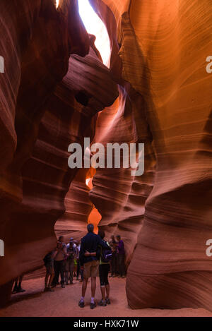 Tourists walking and looking at a section of the sandstone eroded slot canyon in Upper Antelope Canyon, Arizona - Stock Photo