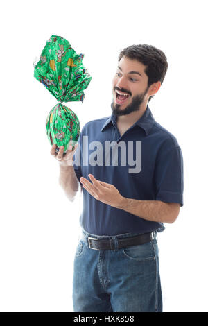 Happy brazilian man holding easter egg stock photo 97397590 alamy young man presents an easter egg wrapped in green paper celebrating holidays with gifts and negle Images