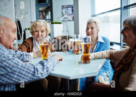 Senior friends gathered in pub - Stock Photo