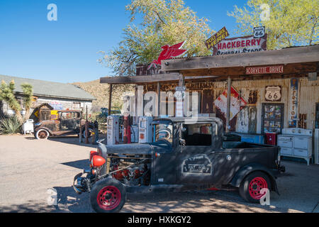 A 1930s pickup and a 2-door sedan in dilapidated condition sit in front of  the general store in Hackberry, Arizona, - Stock Photo