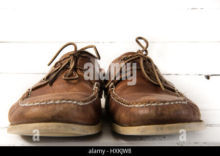 Pair of worn out brown casual leather shoes in front of white wooden background - Stock Photo