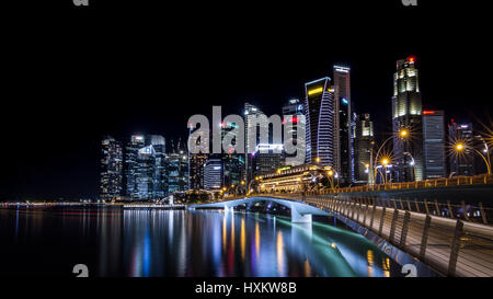Night time view of Jubilee bridge and the cityscape of the skyscraper business district of Singapore City taken - Stock Photo