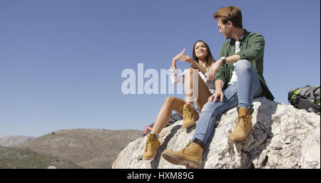 Two young tourists sitting on rock - Stock Photo
