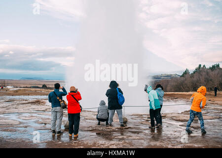 Tourists are watching the eruption of the Strokkur geyser in Iceland. It is part of the Haukadalur geothermal area - Stock Photo