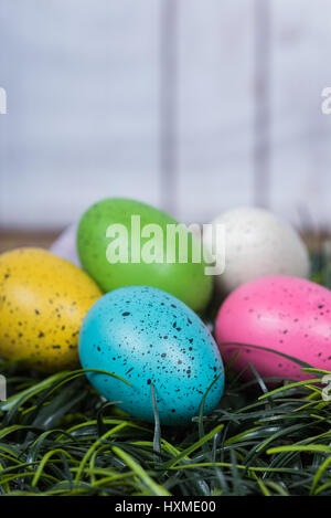 Colorful speckled easter eggs arranged on grass bed - Stock Photo