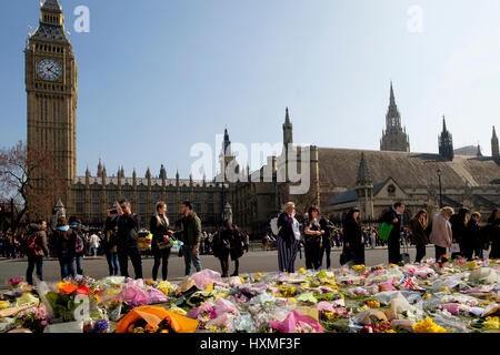 Westminster, London, UK. 27rd Mar, 2017. People contemplate the floral tributes left in Parliament Square to remember - Stock Photo