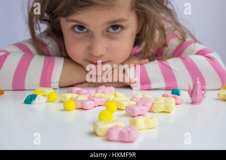 Little girl playing with candies; shallow depth of field - Stock Photo