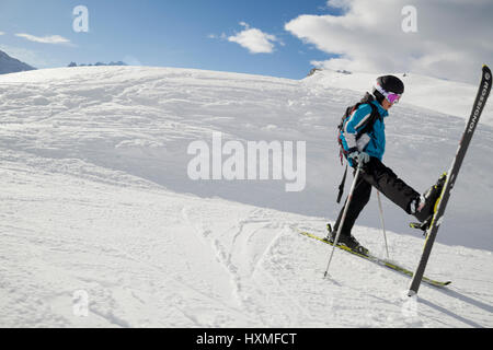 A skier stretches on the side of a trail at Domaine de Balme ski resort in Le Tour outside of Chamonix-Mont-Blanc. - Stock Photo