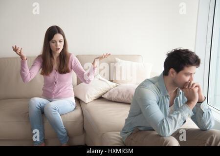 Young couple having dispute. Woman speaking emotionally, sad man - Stock Photo