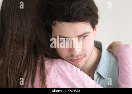 Thoughtful young man embracing lady looking away, lost in though - Stock Photo