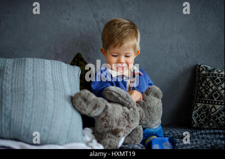 The charming kid plays with a teddy bear. The little boy sits among big pillows and holds with a hand a teddy bear. - Stock Photo