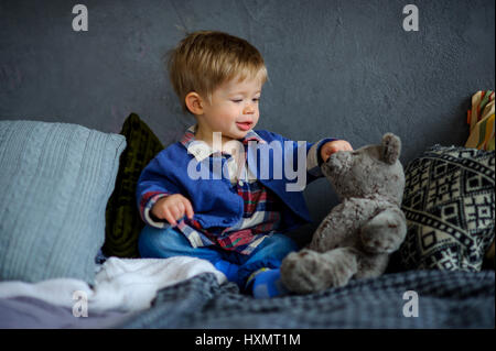 The charming kid plays with a teddy bear. The little boy sits on a bed and touches a finger a soft toy. - Stock Photo