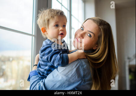 The young woman holds on hands of the little son. She is by the big window. The pretty kid embraces mother. - Stock Photo