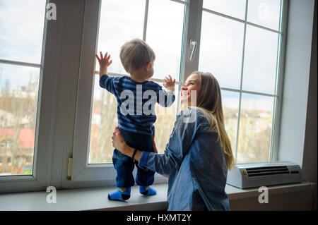 The young woman with the little son are by the big window and look at the street. The kid stands on a window sill, - Stock Photo