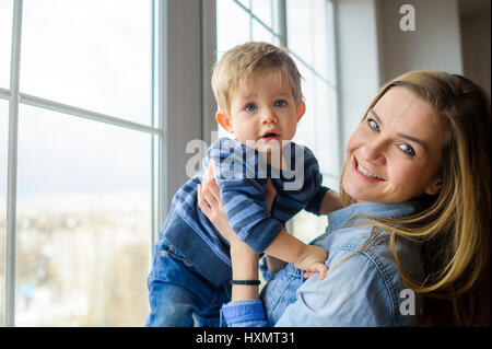 The young woman holds on hands of the little son. She is by the big window. Mother and the son look in the camera. - Stock Photo
