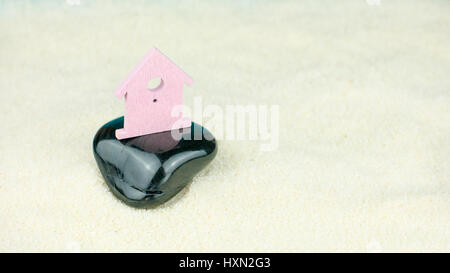 Symbol of little lilac house secured builed on black stone instead on sand - Stock Photo