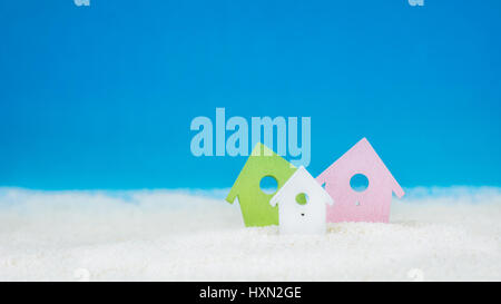 Symbol of tree coloured little houses on the sand on bright blue background - Stock Photo