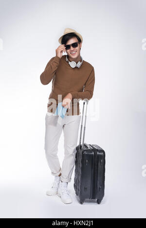Full length of young tourist asian man holding passport with suitcase over grey background - Stock Photo