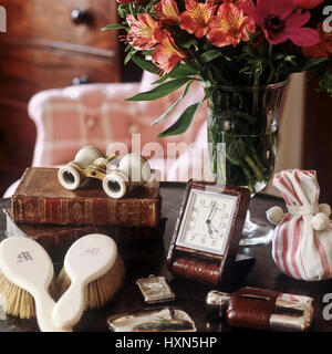 Vase of flowers and antiques on table. - Stock Photo