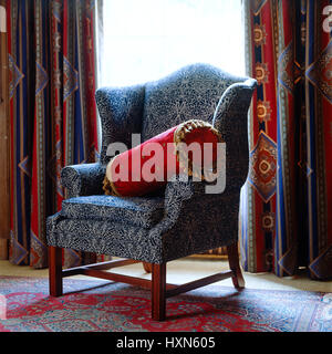 Patterned armchair with red cushion. - Stock Photo
