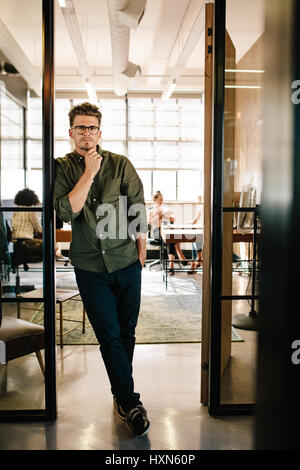 Full length portrait of handsome young man standing in doorway of office with people working in background. - Stock Photo