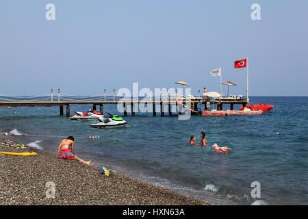 Kemer, Turkey - August 29, 2014: Private pier for boats on a pebble beach Turkish Mediterranean resort, Antalya - Stock Photo