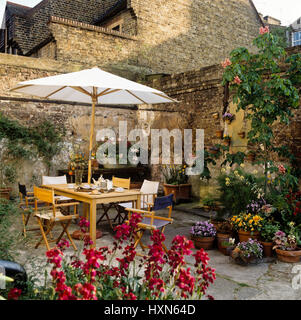 Table and chairs under sun umbrella. - Stock Photo