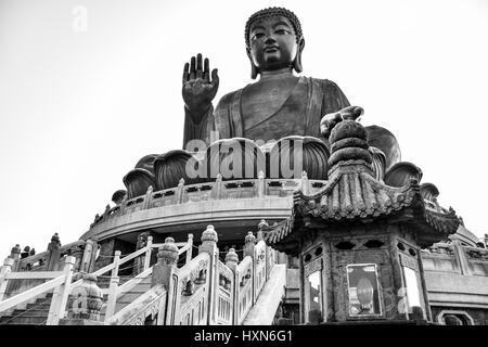 The enormous Tian Tan Buddha (Big Buddha) in black and white color at Po Lin monastery, Hong Kong with copy space - Stock Photo